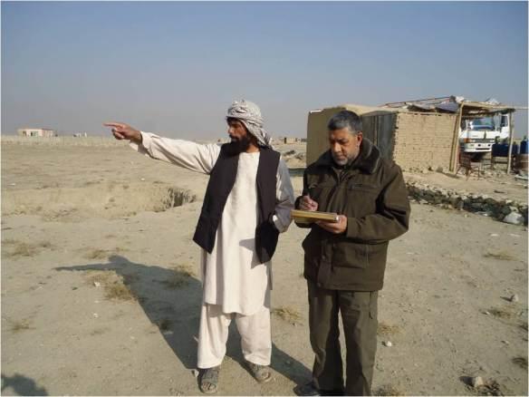 Ахмад Шах,  (слева), местный житель, обсуждает преимущества разминирования с членом группы по разминированию.